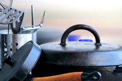 Cast iron and stainless steel cookware on a wooden table. Small blue vessel as a color focus. Reflections. Royalty Free Stock Photo