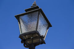 Cast iron streetlight. A black cast iron streetlight with frosted glass against a clear blue sky Royalty Free Stock Image