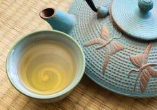 Cast iron tea pot with tea cup Stock Photography