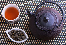 Cast iron TeaPot with teacup and tea leaves Royalty Free Stock Photo
