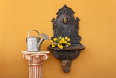 Cast iron wall fountain. Flanked by a greek ionic column  above  with a watering can to water the roses Royalty Free Stock Photos