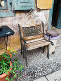 Cast Iron and Wood Bench Outside Old Cafe. An antique single seat wooden bench with cast iron frame and lace, outside an old Greek cafe with faded stucco and royalty free stock images