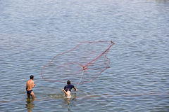 Cast a net. Some fisherman are casting their net into the river. Come and get more experience royalty free stock photo
