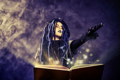 Cast a spell. Little girl in a costume of witch casts a spell over magic book over dark background Stock Photo