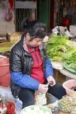 Castañas de agua femeninas de la peladura del verdulero en el mercado Imagen de archivo