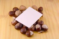 Castañas del otoño en fondo de madera y tarjeta de papel en blanco Fotos de archivo