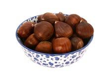 Castañas dulces en cáscaras, en un cuenco azul y blanco de China Foto de archivo libre de regalías