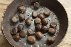 Castagne crude nella pentola per le castagne dell'arrosto Fotografia Stock