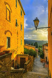 Castagneto Carducci old stone village in Maremma. Picturesque fl. Castagneto Carducci old stone village in Maremma on sunset. Picturesque flowery street and Royalty Free Stock Photo