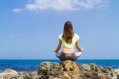 Castana adolescente atletico esegue l'allenamento di yoga vicino Fotografia Stock Libera da Diritti