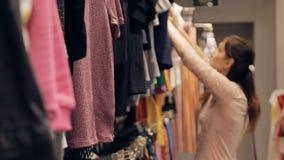 Castana alla moda in vestiti alla moda nel mercato archivi video