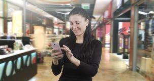 Castana attraente è sorpreso leggere i messaggi sullo smartphone archivi video