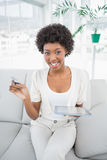Castana attraente facendo uso della sua carta di credito da comprare online Fotografia Stock