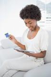 Castana attraente sorridente facendo uso del suo pc della compressa da comprare online Immagine Stock Libera da Diritti