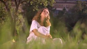 Castana caucasico sorridente dei giovani nel parco che si siede sull'erba, greaming, pensante