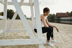 Castana con breve taglio di capelli che si siede sul sedile di pallavolo Fotografia Stock Libera da Diritti
