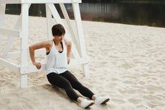 Castana con breve taglio di capelli fa l'allungamento sulla spiaggia del fiume Fotografie Stock