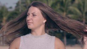 Castana con capelli lunghi sciolti posa sul movimento lento della spiaggia video d archivio
