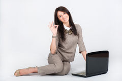 Castana della donna di affari bello in un vestito grigio che lavora con un computer portatile immagine stock libera da diritti