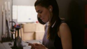 Castana femminile allegro attraente avendo un irrompere lei risolve il programma, mettendo sulle cuffie e selezionandola archivi video