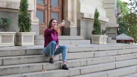 Castana giovane di risata fotografandosi sul telefono, facente selfie stock footage