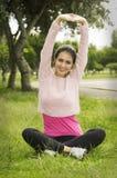 Castana ispano nell'yoga copre la seduta sull'erba Fotografia Stock Libera da Diritti