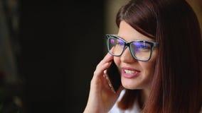 Castana molto bello con il razgovarivaet di vetro che sorride facendo uso di un telefono cellulare Primo piano stock footage