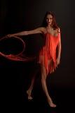 Castana nel rosso su una ginnasta scura del ballerino del fondo Immagini Stock