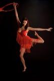 Castana nel rosso su una ginnasta scura del ballerino del fondo Immagine Stock