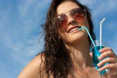 Castana in occhiali da sole che bevono un cocktail Immagini Stock