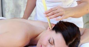 Castana rilassato ottenendo un trattamento d'esame in controluce dell'orecchio stock footage