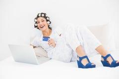 Castana in rulli dei capelli e scarpe del cuneo facendo uso del suo computer portatile allo sho Fotografia Stock Libera da Diritti