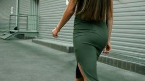 Castana scarno con le natiche sexy in vestito cammina sulla città video d archivio