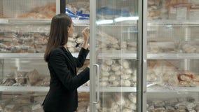 Castana scelga il pane congelato dal frigorifero, donna che seleziona la pagnotta al supermercato archivi video