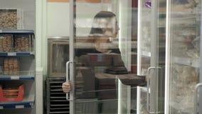 Castana scelga il pane congelato dal frigorifero, donna che seleziona la pagnotta al supermercato stock footage