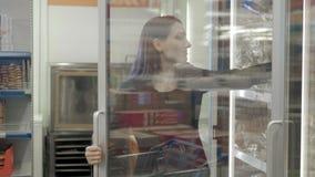 Castana scelga il pane congelato dal frigorifero, donna che seleziona la pagnotta al supermercato video d archivio