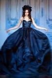 Castana sensuale dai capelli lunghi con una corona dei fiori neri stan Fotografia Stock Libera da Diritti