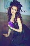 Castana sensuale dai capelli lunghi con una corona del nero fiorisce il sitt Immagine Stock Libera da Diritti