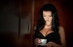 Castana sexy attraente con il reggiseno nero che tiene una tazza di caffè bianca Ritratto della donna sensuale nella scena classi Immagine Stock