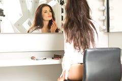 Castana sexy in camicia bianca che si siede sul volto dal mirr Fotografie Stock