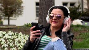 Castana si siede su un banco della via ed ascolta musica stock footage