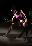 Castana splendido sollevando alcuni pesi e lavorando al suo bicipite in una palestra Donna di forma fisica che fa allenamento Rag Fotografie Stock