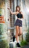 Castana sveglio con la minigonna che posa su una via della città Fotografia Stock Libera da Diritti