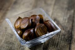 Castanhas comestíveis saborosos em uma mesa de cozinha de madeira Castanhas em t Fotografia de Stock