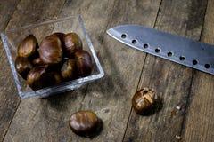 Castanhas comestíveis saborosos em uma mesa de cozinha de madeira Castanhas em t Imagens de Stock Royalty Free