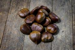 Castanhas comestíveis saborosos em uma mesa de cozinha de madeira Castanhas em t Foto de Stock