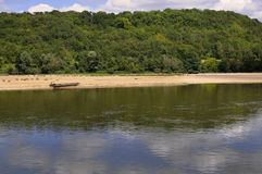Castaway. A wooden boat alone on a beach by the river Stock Image