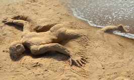 Castaway. Man sculpted in the sand, representing a castaway on a beach Royalty Free Stock Images