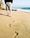 Castaway walking to his shelter - Beach Series. A castaway's foot steps leading to his shelter Stock Images