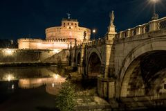 Castel and Ponte Sant`Angelo at night, Rome, Italy. This place is a famous old landmark of Rome. Panorama of medieval castle and bridge in the Rome city center stock image